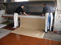 Gewaschene Teppiche werden in Schleudermaschine zum Trocknen eingelegt.