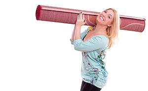 Frau trägt zusammengerollten Teppich zur Teppichreinigung