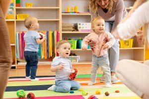 3 Babys spielen auf Teppich im Kindergarten