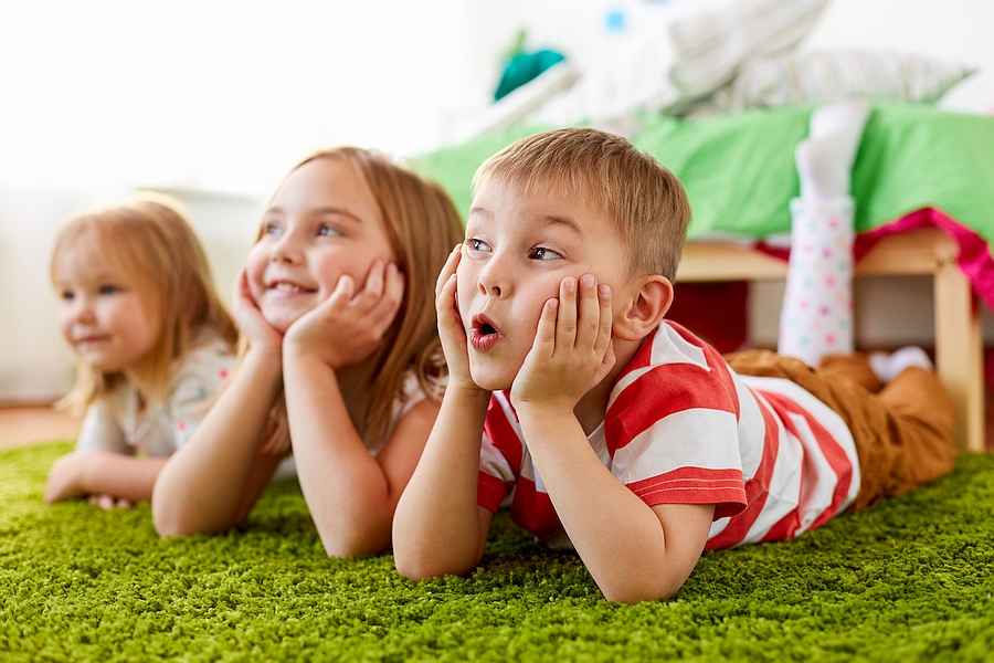 Drei Kinder lümmeln auf dem Teppich