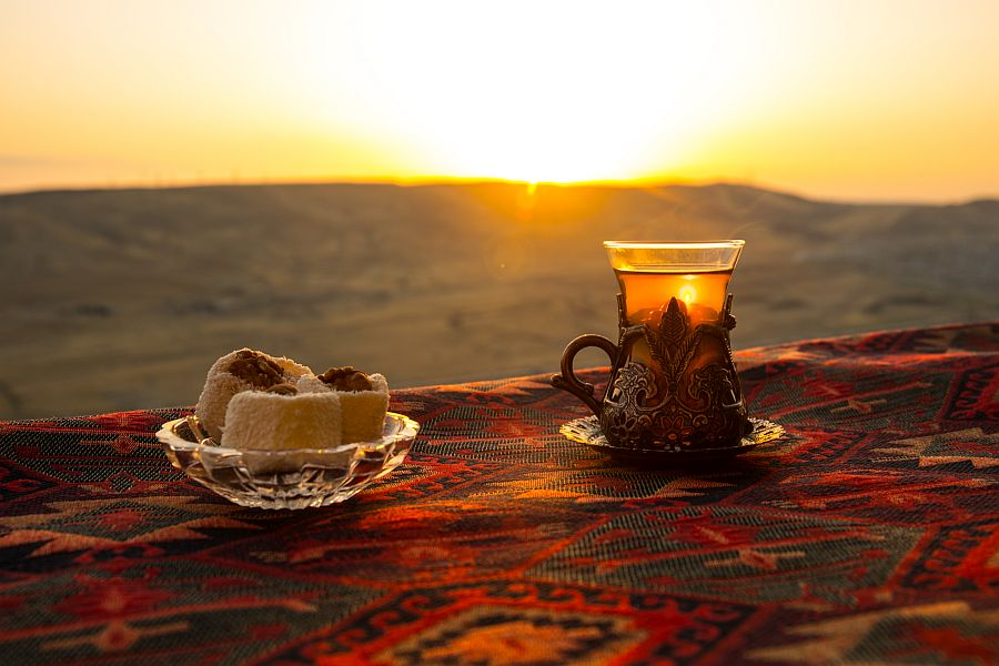 Orientteppich, Sonnenuntergang, traditionelles Teeglas und orientalische Süßigkeit auf dem Orientteppich